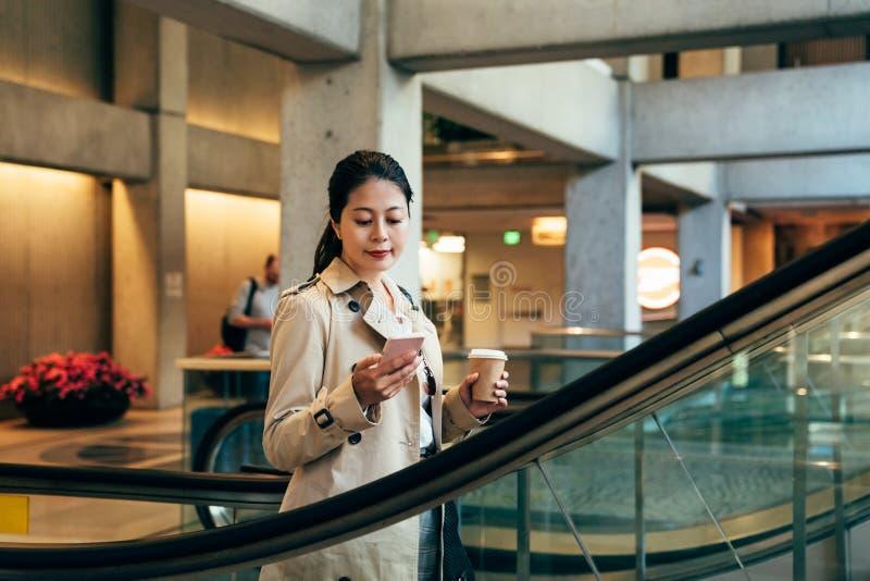 Junge asiatische Büroangestelltstellung auf Rolltreppe stockbilder