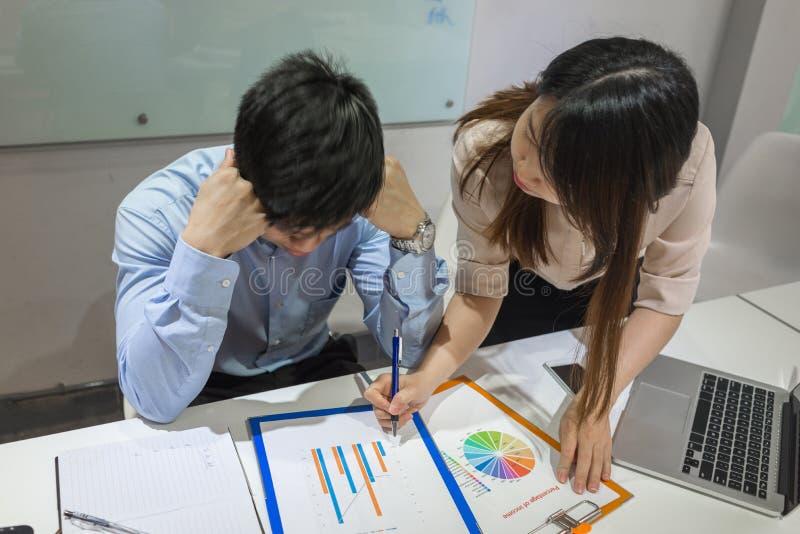 Junge asiatische Bürodame, die ihr Partner zeigt, berichtet stockfotografie