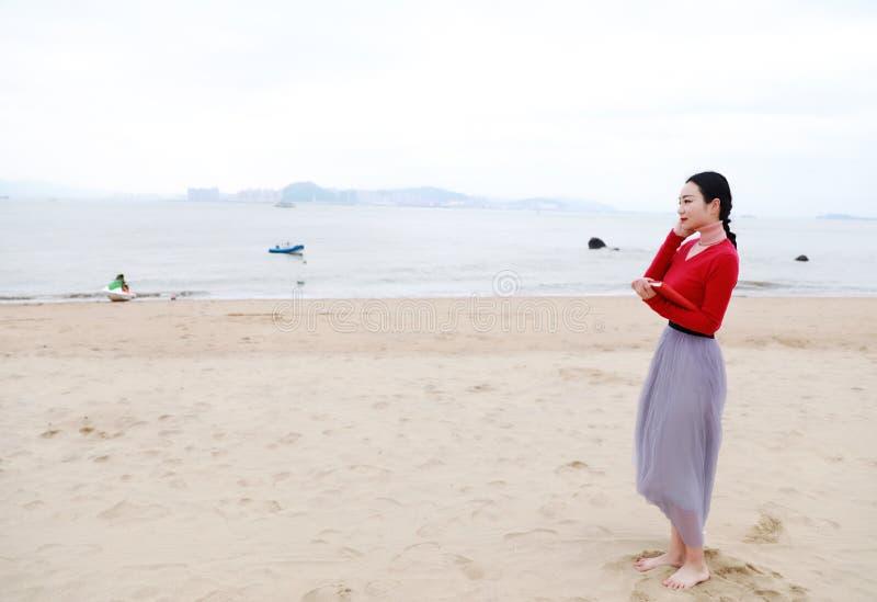Junge asiatische chinesische Frau mit Buch und auf den Musikweg entlang Sand-Strand hören lizenzfreies stockbild