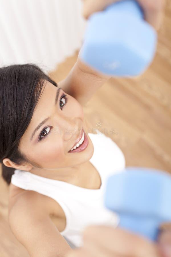 Junge asiatische chinesische Frauen-anhebende Gewichte an der Gymnastik lizenzfreie stockbilder