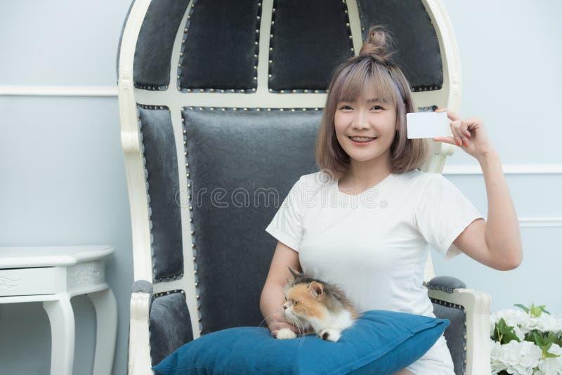 Junge asiatische Dame sitzen auf Sofahandgriffkreditkarte mit weniger Katze auf Kissen, kaufendes on-line-Konzept lizenzfreie stockbilder