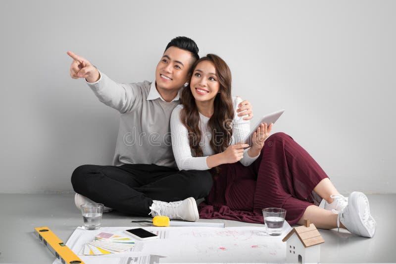 Junge asiatische erwachsene Paare, die auf Flor plant neues Haupt-desig sitzen lizenzfreie stockfotos
