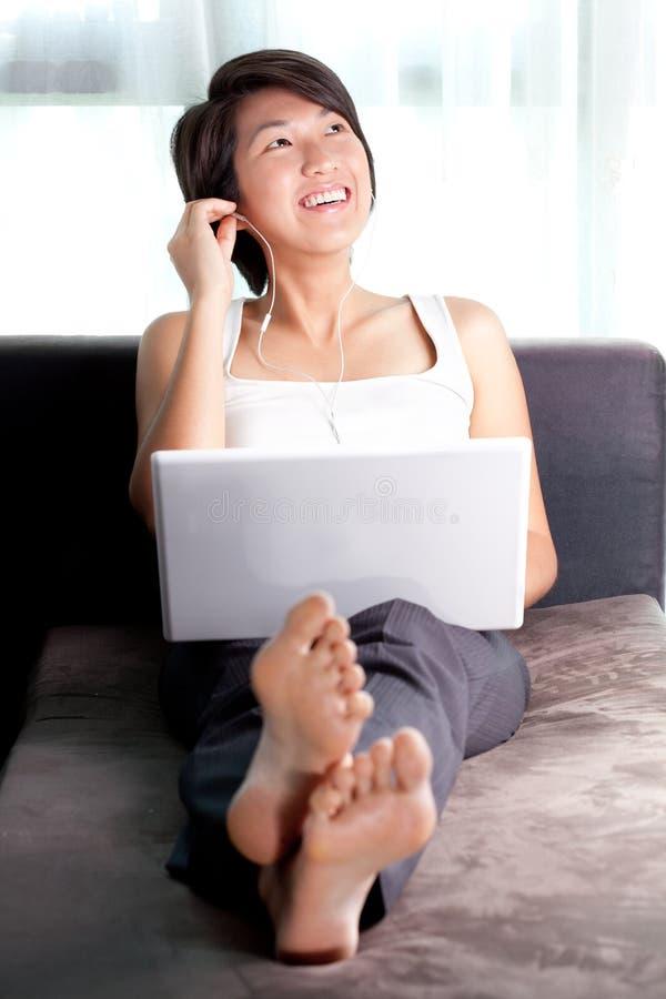 Junge asiatische Executiventspannung auf dem Couchhören stockbild