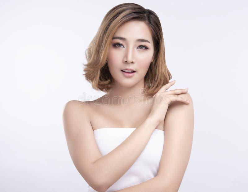 Junge asiatische Frau der Sch?nheit mit perfekter Gesichtshaut Gesten f?r Anzeigenbehandlung Badekurort und Cosmetology stockbild