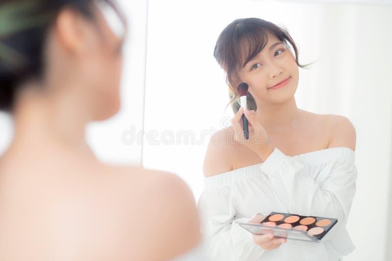 Junge asiatische Frau des Schönheitsporträts, die mit dem Gesicht schaut den Spiegel anwendet Make-up mit Bürstenbacke im Schlafz stockbilder