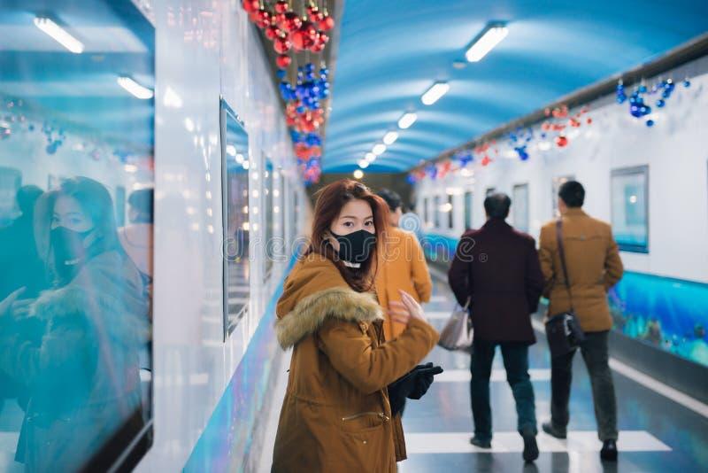 Junge asiatische Frau, die auf Bahnstation wartet stockbild