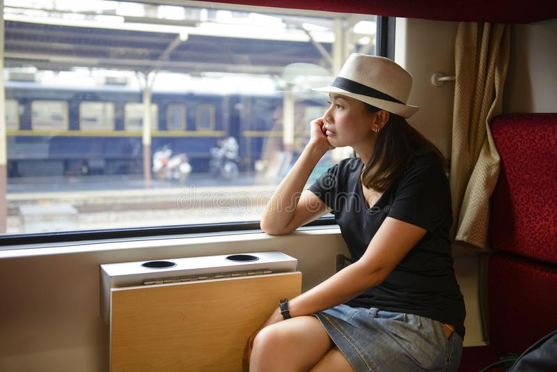 Junge asiatische Frau, die das Fenster beim Sitzen heraus schauend im Zug reist stockbilder