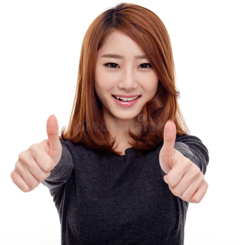 Junge asiatische Frau, die Daumen zeigt stockfotos