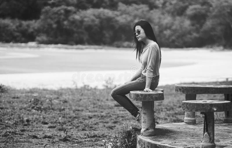 Junge asiatische Frau, die die sunglass sitzen auf Marmorstuhl nahe dem Strand, Schwarzweiss--, trauriges Konzept, selektiver Fok lizenzfreie stockfotografie