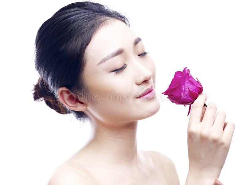 Junge asiatische Frau, die Duft der Rotrose genießt lizenzfreies stockbild