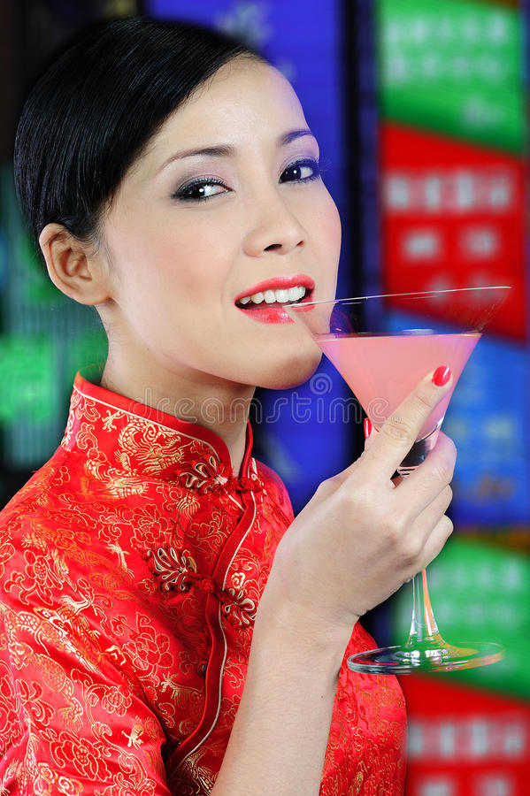 Junge asiatische Frau, die ein Glas des Cocktails anhält lizenzfreies stockfoto