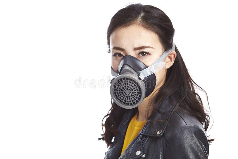 Junge asiatische Frau, die eine Gasmaske trägt stockbild