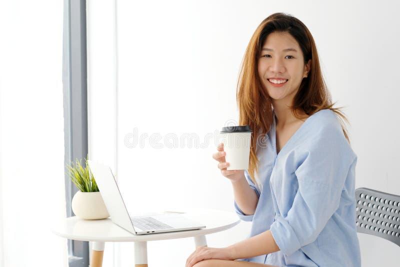 Junge asiatische Frau, die eine Kaffeetasse mit lächelndem Gesicht, positi hält stockbild