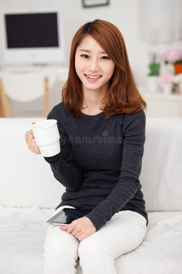Junge asiatische Frau, die einen Auflage PC verwendet lizenzfreie stockbilder