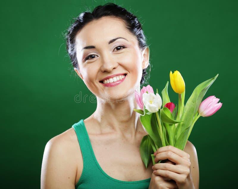 Junge asiatische Frau, die einen Blumenstrauß von Tulpen hält stockfotografie