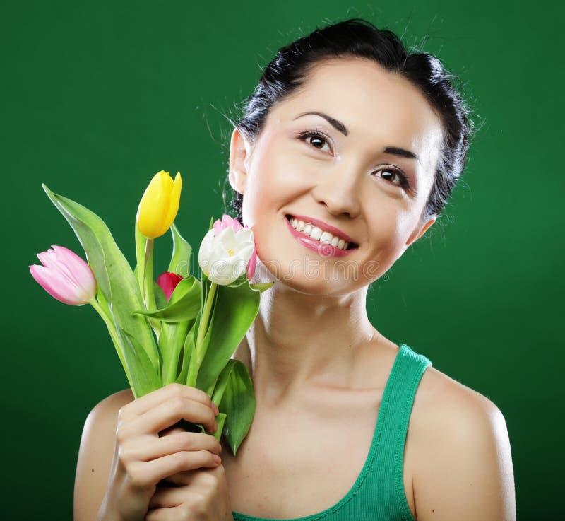 Junge asiatische Frau, die einen Blumenstrauß von Tulpen hält lizenzfreie stockfotografie