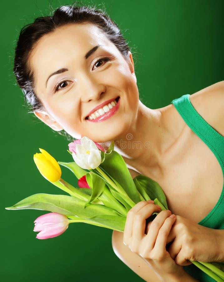 Junge asiatische Frau, die einen Blumenstrauß von Tulpen hält stockfotos