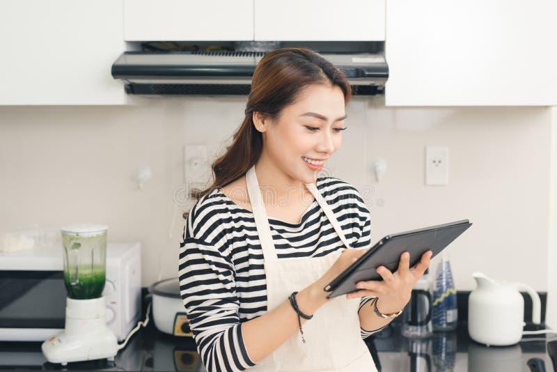 Junge asiatische Frau, die einen Tablet-Computer verwendet, um in ihrer Küche zu kochen lizenzfreies stockbild