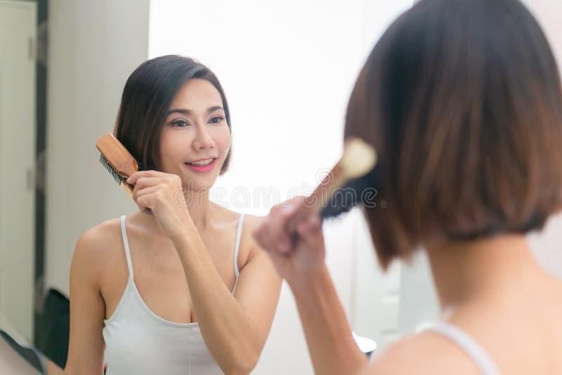 Junge asiatische Frau, die gesundes Haar vor einem Spiegel bürstet lizenzfreie stockfotografie