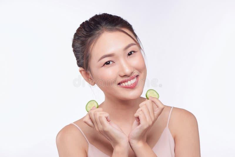 Junge asiatische Frau, die Gurkenscheibe in ihren H?nden lokalisiert auf wei?em Hintergrund h?lt und isst lizenzfreies stockfoto
