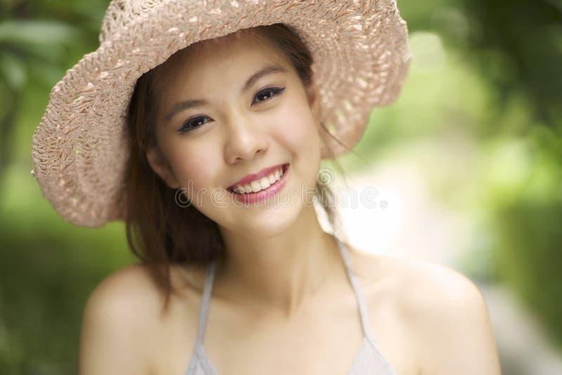 Junge asiatische Frau, die hell an im Freien lächelt stockfotos