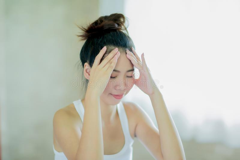 Junge asiatische Frau, die ihren Kopf massiert stockbild