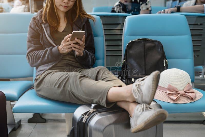 Junge asiatische Frau, die intelligentes Telefon am Flughafen verwendet stockfotografie
