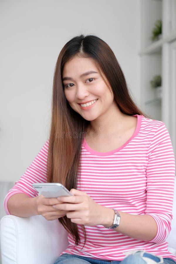 Junge asiatische Frau, die intelligentes Telefon mit dem Lächeln verwenden, glücklich und wirklich stockbild