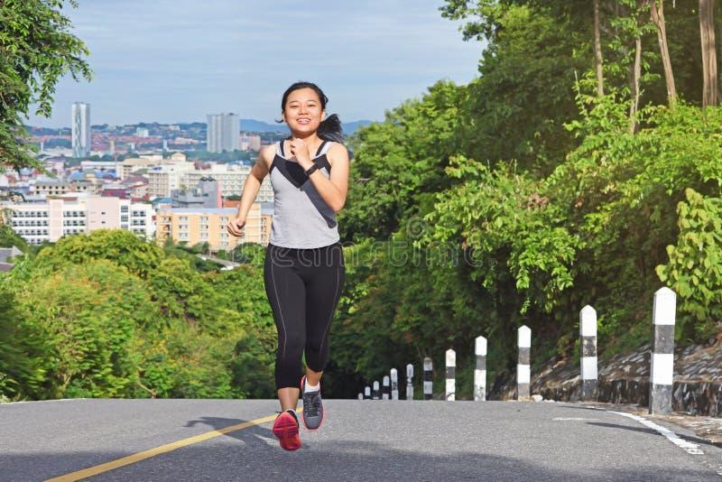 Junge asiatische Frau, die in lächelndem glücklichem Betrieb des Parks rüttelt lizenzfreies stockbild