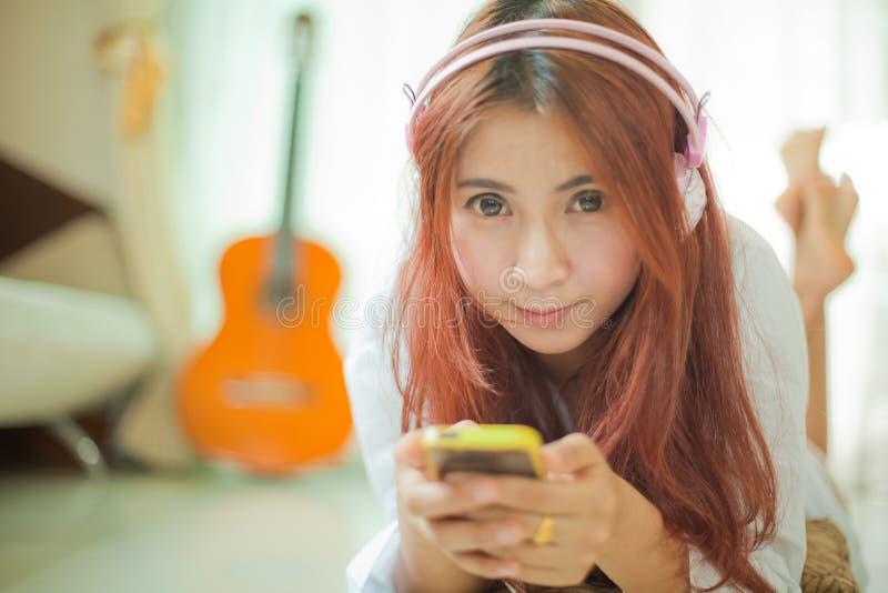 Junge asiatische Frau, die Musik hört lizenzfreie stockbilder