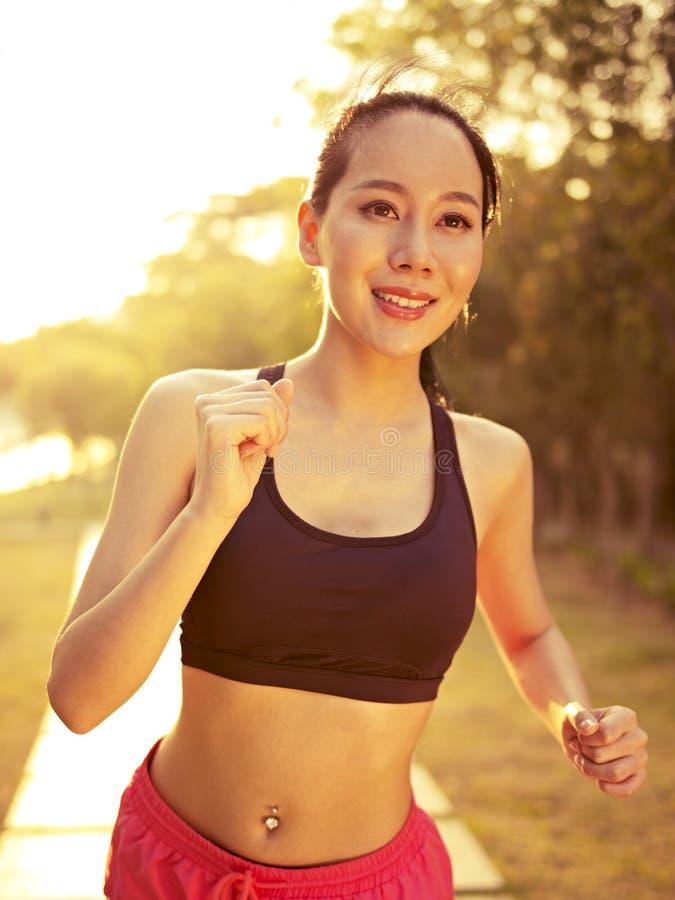 Junge asiatische Frau, die in Park läuft stockfoto