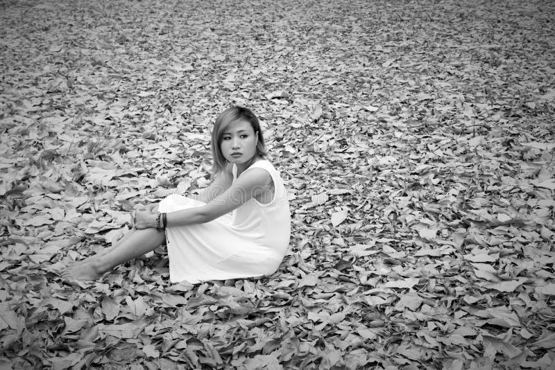 Junge asiatische Frau, die traurig auf trockenem Blatt im Wald allein sitzt stockbilder