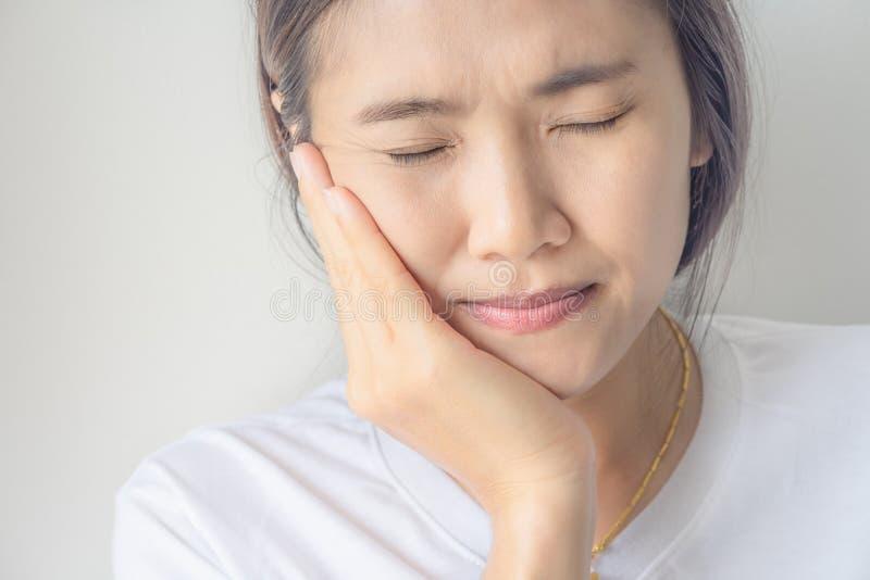 Junge asiatische Frau, die unter Zahnschmerzen leidet lizenzfreie stockfotografie