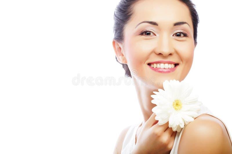 Junge asiatische Frau, die weiße gerber Blume hält lizenzfreie stockfotografie