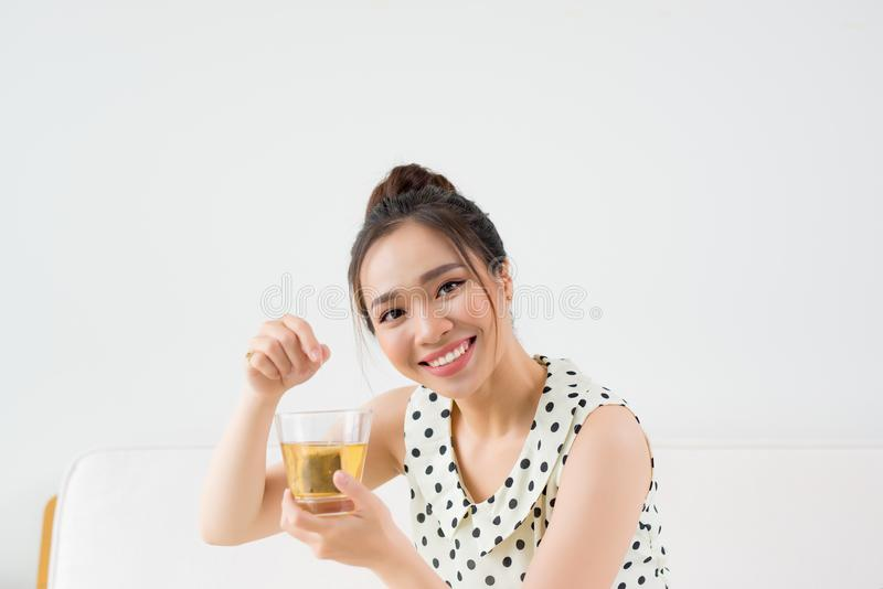 Junge asiatische Frau, die zu Hause auf Couch und trinkendem Tee sitzt lizenzfreie stockbilder