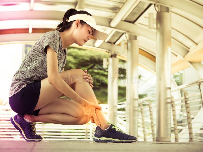 Junge asiatische Frau hat die Beinschmerz, nach Übungstraining Lifest lizenzfreie stockbilder