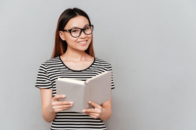 Junge asiatische Frau im Glaslesebuch stockfoto