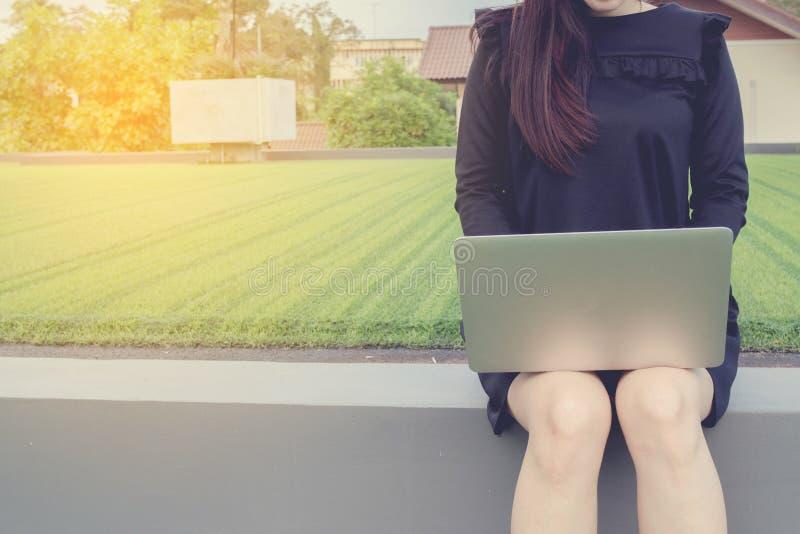 Junge asiatische Frau im schwarzen Hemd unter Verwendung des Laptops am äußeren Haus herein lizenzfreies stockfoto