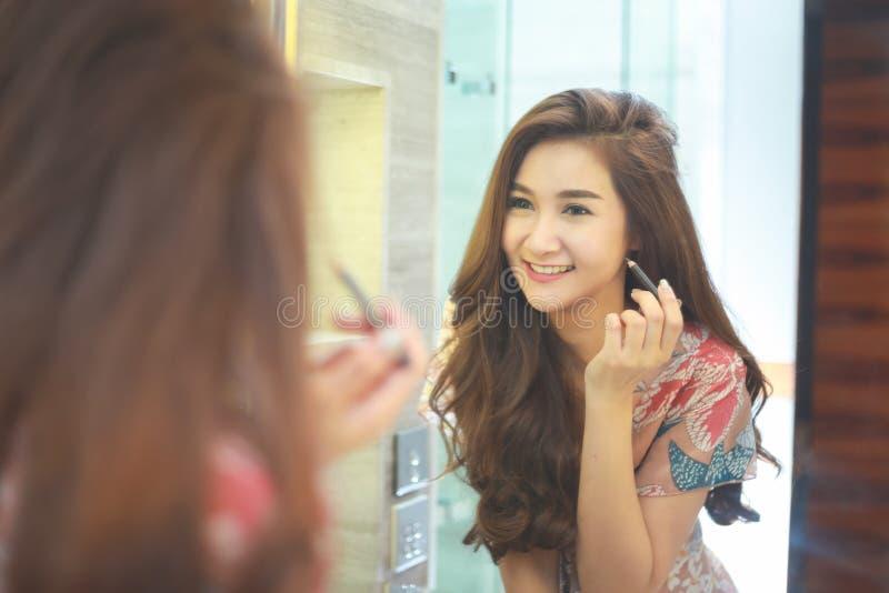 Junge asiatische Frau ist enttäuscht von ihrer Fähigkeit, Make-up anzuwenden Augenlider lizenzfreie stockfotografie