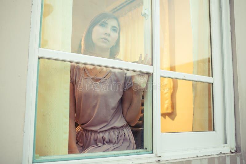 Junge asiatische Frau ist am Fenster traurig stockbilder