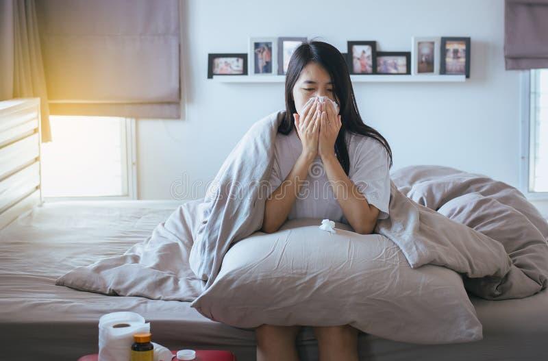 Junge asiatische Frau mit dem kalten Schlag und laufende Nase auf Bett, krankes weibliches Niesen stockfotografie