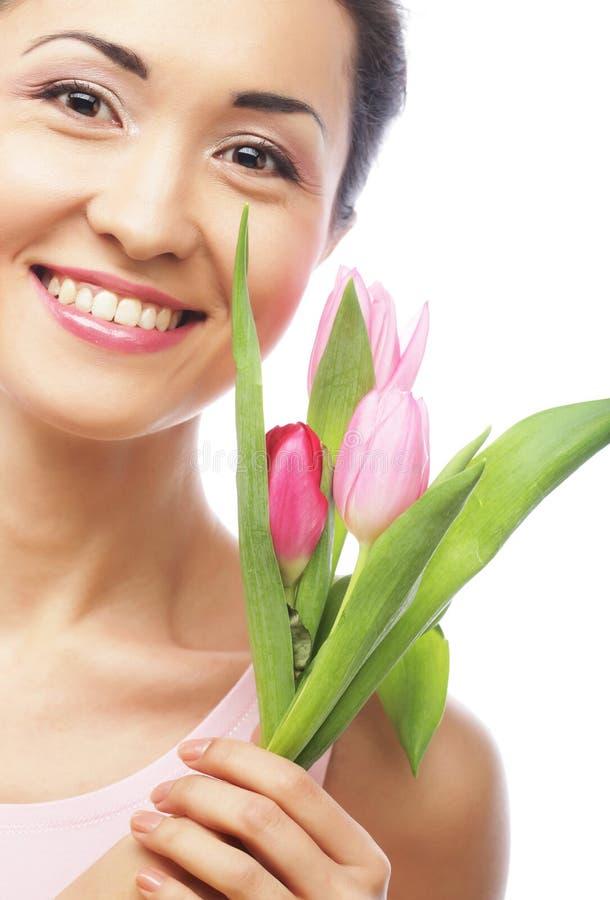 Junge asiatische Frau mit Tulpen lizenzfreies stockbild