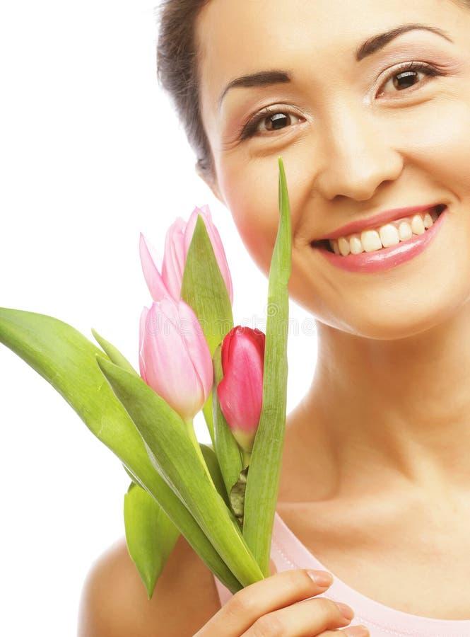 Junge asiatische Frau mit Tulpen lizenzfreie stockfotos