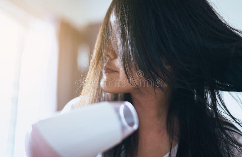 Junge asiatische Frau nach dem Bad, das ihr Haar mit Kamm, weiblicher Trockner ihr langes Haar mit Trockner hairbrushing ist stockfoto