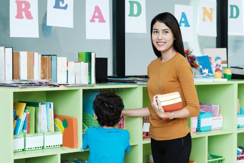Junge asiatische Frau, welche die Bücher stehen mit Jungen an Bibliotheks-BAC hält lizenzfreies stockfoto