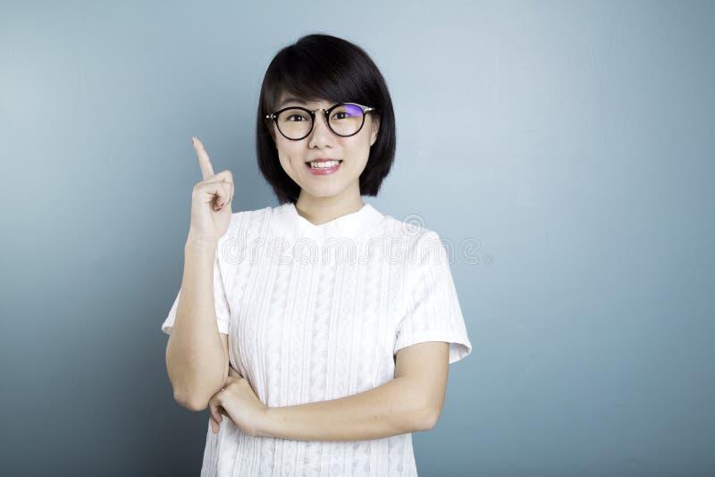 Junge asiatische Frauen, die auf blauem Hintergrund denken lizenzfreies stockbild