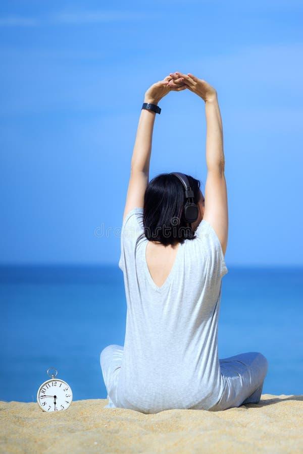 Junge asiatische Frauen, welche die Kopfh?rer, h?rend Musik am Strand tragen Wei?er Wecker gesetzt auf den Sand Blaues Meer und H stockbild