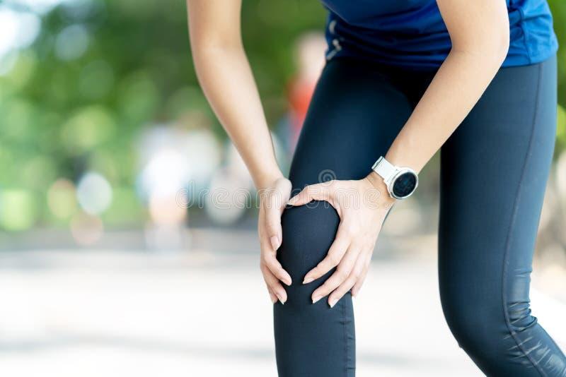 Junge asiatische Frauenholding-Knieschmerz, wenn morgens allgemeiner Naturpark laufen gelassen wird Gemeinsame Verletzung im Athl stockbilder