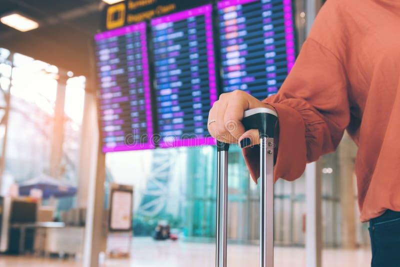 Junge asiatische Frauenstellung am Flughafenholdingkoffer, der Abfahrt mit dem Flugplan im Hintergrund überprüft lizenzfreies stockbild