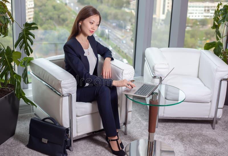 Junge asiatische Geschäftsfrau in der Klage, die an einem Laptop arbeitet stockbild